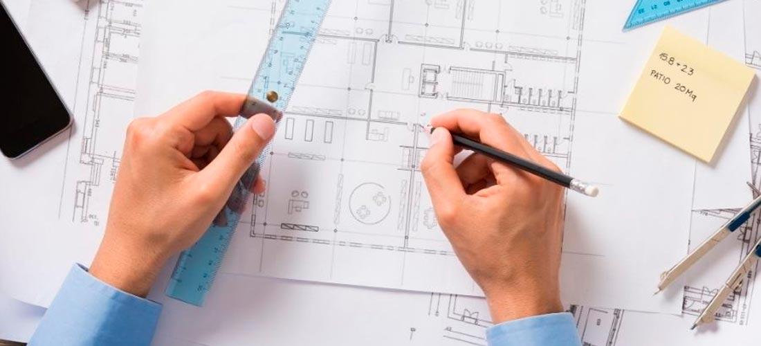Imagen de un arquitecto analizando los planos de una vivienda para licitar una cédula de habitabilidad
